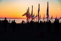 Leute am Strand aus verschiedenen Ländern mit dort Flagge lizenzfreie stockfotografie