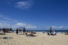 Leute am Strand mit Stadt auf dem Hintergrund Lizenzfreies Stockfoto