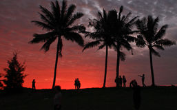 Leute am Strand während des Sonnenuntergangs Lizenzfreie Stockbilder