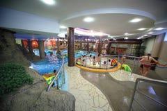 Leute Swim auf aufblasbaren Kreisen im Pool Stockbilder