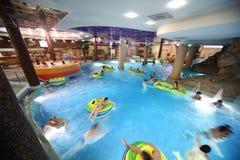 Leute Swim auf aufblasbaren Kreisen im Pool Lizenzfreie Stockfotografie