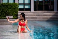 Leute-, Technologie-, Reise-, Tourismus- und Sommerkonzept - glückliche junge Frau beim Bikinibadeanzug- und -Sonnenbrillenehmen Lizenzfreies Stockfoto