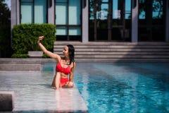 Leute-, Technologie-, Reise-, Tourismus- und Sommerkonzept - glückliche junge Frau beim Bikinibadeanzug- und -Sonnenbrillenehmen Stockbilder