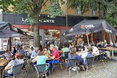 Leute trinken, essen und sprechen auf der Terrasse eines Cafés Stockbild