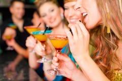 Leute in trinkenden Cocktails des Klumpens oder des Stabes Stockfotos