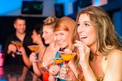 Leute in trinkenden Cocktails des Klumpens oder des Stabes Stockfoto