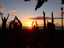 Leute tun Sonnenuntergangyoga für Nächstenliebe auf Waikiki-Strand mit Fläche herein Stockfotografie