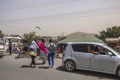 Leute und Autos auf der Straße Lizenzfreies Stockbild