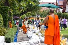 Leute und Mönch, die Sandsäcke holen, um Flut zu verhindern stockfotografie