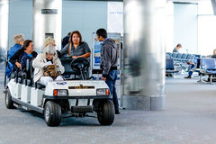 Leute und Passagiere, die in motorisierte Warenkörbe im Flughafen reiten Lizenzfreie Stockbilder