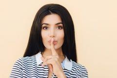 Leute und Stillekonzept Attraktive Frau mit Ruhezeichen hält Vorderfinger auf Lippen, bittet, ruhig zu sein, während jemand schlä stockfotografie