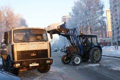 Leute und Techniken säubern Schnee von der Straße Lizenzfreies Stockfoto