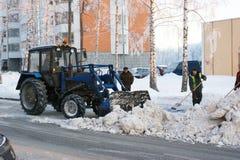 Leute und Techniken säubern Schnee von der Straße Stockfotos