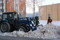 Leute und Techniken säubern Schnee von der Straße Stockfoto