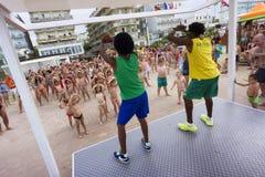 Leute und viele Kinder, die mit dem Animationsteam des Erholungsortes tanzen Stockbild