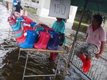 Leute verkaufen Plastikstiefel durch die Straße in einem überschwemmten Rangsit, Thailand, im Oktober 2011 Stockbilder