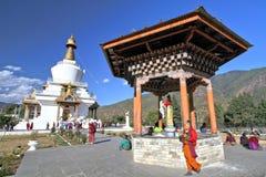 Leute von Bhutan im Trachtenkleid mit tibetanischem Gebetsrad Stockbild
