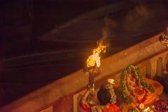 Leute von Indien, das Zeremonie in Varanasi, mit Feuer auf den Banken des Messgerät-Flusses durchführt stockfotos