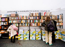 Leute wählen alte Bücher auf Antiquitätensstand Stockbild