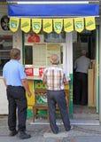 Leute warten in Linie am Shop mit Lottoscheinen Stockbilder