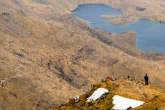 Leute, welche die Ansicht von einem Berg genießen Stockbilder