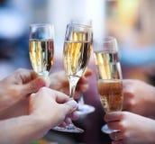 Leute, welche die Gläser Champagner einen Toast machend anhalten Stockfotos