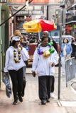 Leute, welche die lustigen Kostüme feiern berühmten Mardi Gras-Karneval auf der Straße im französischen Viertel tragen Lizenzfreie Stockfotos