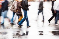 Leute, welche die nasse Straße kreuzen Lizenzfreie Stockfotografie