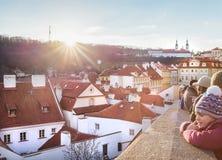 Leute, welche die Sonne und die große Ansicht über Prag-Öffnung vom Schloss während des Weihnachtstages genießen Stockbilder