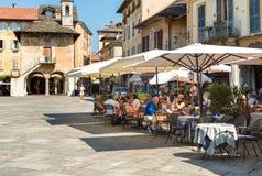 Leute, welche die Stange im Freien in der historischen Mitte des alten Dorfs von Orta San Giulio, herein gelegen auf der Küste vo stockfotos