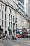 Leute, welche die Straße auf einem Fußgängerübergang vor rotem Bus in der Stadt von London, Großbritannien kreuzen stockbilder