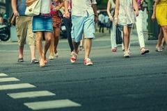 Leute, welche die Straße kreuzen Stockfotografie