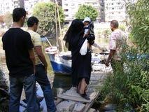 Leute, welche oben die andere Seite vom Nil durch Schiff Abschluss des Fischermannes im Hafenschiff im Fluss Nil im maadi Kairo k Stockfotografie