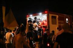 Leute werden genommen zu den Krankenwagen nachdem man Schmerzen während des Zusammentreffens mit Bereitschaftspolizei gewesen ist lizenzfreies stockfoto