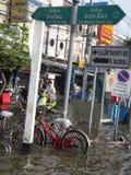 Leute werden mit Wasser in einer überschwemmten Straße in Rangsit, Thailand, im Oktober 2011 fertig stockbilder