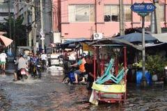 Leute werden mit Wasser in einer überschwemmten Straße in Rangsit, Thailand, im Oktober 2011 fertig lizenzfreie stockfotos