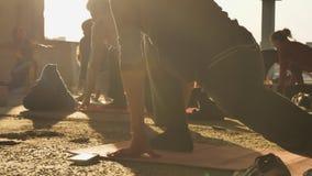 Leute Yogis tun Yoga mit Trainer in verlassenem Gebäude im Sommer auf dem Sonnenuntergang, Reflexionen in camera, gesund stock video footage
