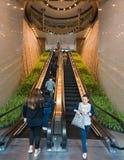 Leute ziehen auf Rolltreppen im zwei Austausch-Quadrat um stockfotos
