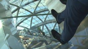 Leutebeine, die auf transparenten Boden auf hoher Stufe in der Ausstellung gehen stock video footage