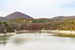 Leutebootfahrt um die Sumpfzypressenbäume und Weg entlang dem Ufer von einem See unter den Bergen am warmen Herbstabend Lizenzfreie Stockbilder