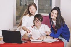 Leutefreunde, die zu Hause am Tisch arbeiten Stockbild