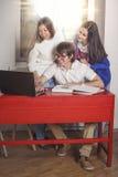 Leutefreunde, die zu Hause am Tisch arbeiten Stockfotografie