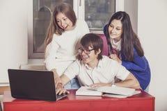 Leutefreunde, die zu Hause am Tisch arbeiten Lizenzfreies Stockbild
