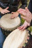 Leutehände, die Musik an djembe Trommeln spielen Lizenzfreie Stockbilder