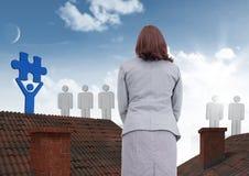 Leuteikonen mit Puzzlespiel bessern die Geschäftsfrau aus, die auf Dächern mit Kamin und und blauem Himmel steht Lizenzfreie Stockfotos