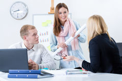 Leutelächeln an einander bei der Arbeit Lizenzfreie Stockbilder