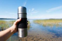 Leutereisender hält Hände eine Thermosflasche Kaffee Stockfotografie