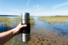 Leutereisender hält Hände eine Thermosflasche Kaffee, auf einem Hintergrund von einem schönen See Lizenzfreie Stockfotografie