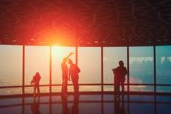 Leuteschattenbilder auf einem Sonnenuntergang im Großen Bürofenster mit einer Stadtansicht lizenzfreies stockbild