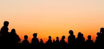 Leuteschattenbilder, die Sonnenunterganghimmel aufpassen Lizenzfreie Stockfotografie